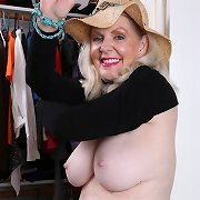 Breasty older babe spreads pussy in closet.