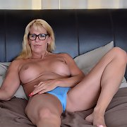 Specky blonde housewife entertains herself on bed