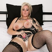 Tattooed mature lady in stockings stroking her vag